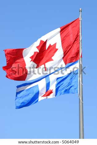 Canadian flag and the official flag of Toronto against the blue sky.