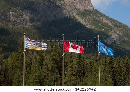 Canadian flag, British Columbia flag and Alberta flag blowing in the wind in the Canadian alpine.