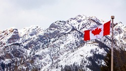 Canadian flag flies high with the majestic mountains behind.