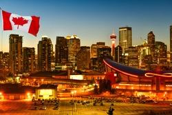Canadian flag in Calgary city skyline at twilight time, Alberta,Canada
