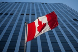 Canadian flag in front of a business building in Ottawa, Ontario, Canada. Ottawa is the capital city of Canada, and one of the main economic, political and business hubs of North America