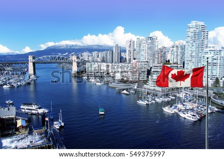 Photo of  Canadian flag in front of view of False Creek and the Burrard street bridge in Vancouver, Canada.