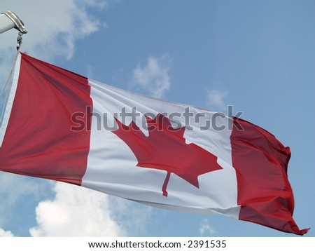 canadian flag on a blue sky - stock photo