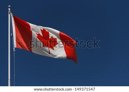 Canadian flag on pole with dark blue sky