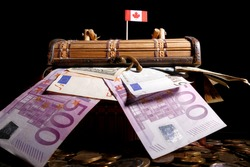 Canadian flag on top of crate full of money