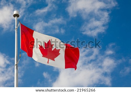 Canadian flag waiving against blue sky with few clouds