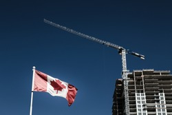 Canadian flag with apartment building under construction in the background, Canadian economy and housing market