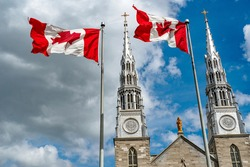 Canadian flags in the forefront of the Notre-Dame Cathedral Basilica in Ottawa. Canada