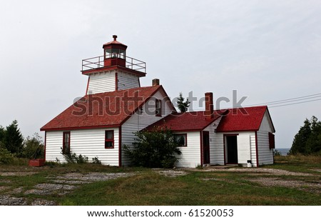 Canadian lighthouse against blue sky with cloud cover