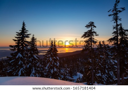 Canadian Nature Landscape covered in fresh white Snow during colorful and vibrant winter sunset. Taken in Seymour Mountain, North Vancouver, British Columbia, Canada.