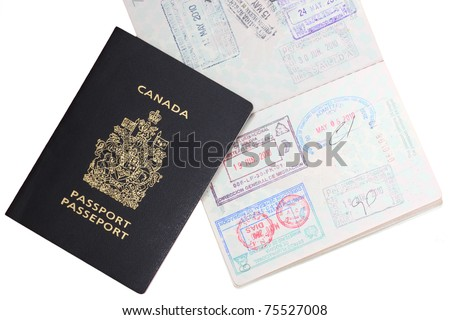 Canadian passports with entrance stamps on white - stock photo