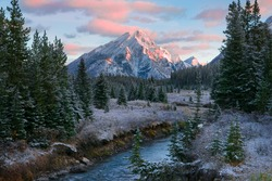 Canadian Rocky Mountain nature scene during a beautiful sunrise with a dusting of overnight snow and frost on the trees and ground.