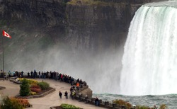 Canadian viewing area at Horseshoe Falls, Niagara Falls, Ontario, Canada with Canadian flag in the foreground. The differences between the US and Canada might be represented by the Niagara chasm