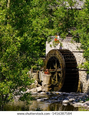 Canadian Water-Wheel Grain Mill, a stone and log built structure of the 1800's, powered by the red river flowing through Winnipeg nestled in trees and greenery both color and Black White version #1416387584