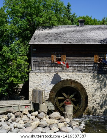 Canadian Water-Wheel Grain Mill, a stone and log built structure of the 1800's, powered by the red river flowing through Winnipeg nestled in trees and greenery both color and Black White version #1416387587