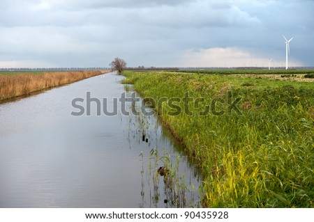 Canal and wind turbine under grey clouds, Holland, Europe