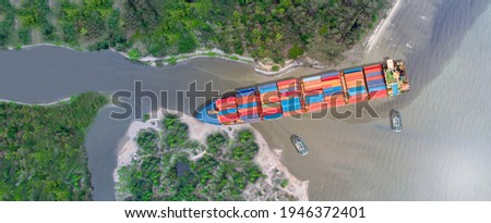 Canal blocked by huge cargo container ship; Aerial top view of accident container ship a stranded ship with salvage crews across the canal concept accident safety and insurance. Foto stock ©
