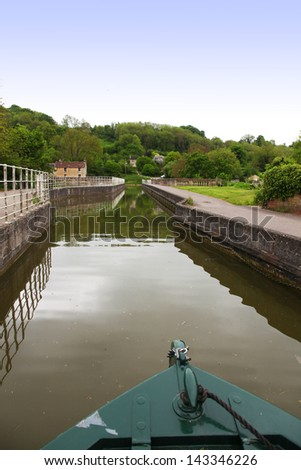 canal boat entering lock with trees, reflection, cottage and bridge in united kingdom near Bath
