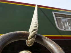 Canal boat mooring, rope attached to a rusted ring with boat in the background with window, looking up close