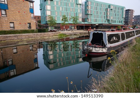 Canal boat, Regent's Canal, London with long boat or barge moored and buildings on far side reflected in calm morning water. #149513390