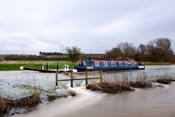 Canal boat stuck trapped in flooded high river overflowing river lock with water flowing at speed into fields and tow path during heavy rain and severe weather causing UK floods on Trent