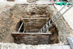 Canal construction work in the city center with ladder, supporting walls and working material - Top view shaft