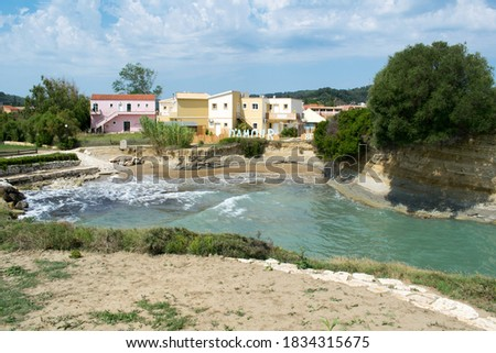 Photo of  Canal d'Amour with nearby colorful houses in Sidari resort town on Corfu island, Greece