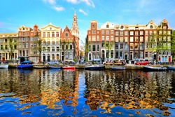 Canal houses of Amsterdam at dusk with vibrant reflections, Netherlands