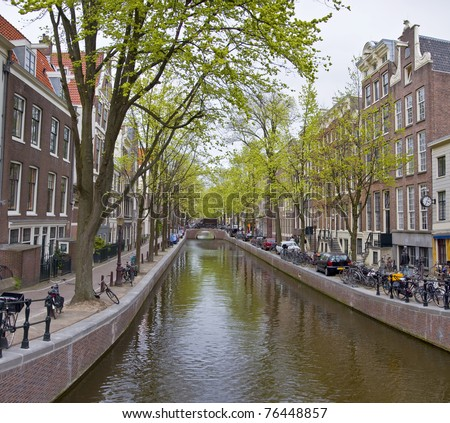 Canal in Amsterdam. Spring cityscape. Bicycles are on the waterfront.