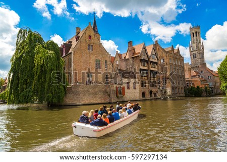 Canal in Bruges and famous Belfry tower on the background in a beautiful summer day, Belgium #597297134