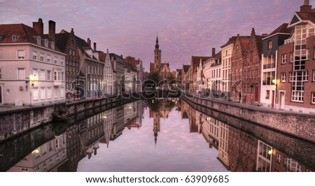 Canal in Bruges, Belgium, at dawn with the street ligts still burning, and lit by a rare pink sky filled with little clouds