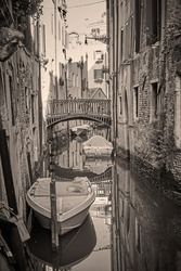 Canal in Venice with bridge and boats, Italy. Black and white vintage style photography, sepia toned venetian view