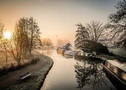 Canal narrow river boats at foggy dawn sunrise with beautiful mist orange haze wood burning smoke from chimneys silhouette trees with sun behind rising
