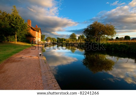 canal, towpath and locks with the sky reflecting in the water