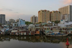 canal waterfont buildings in Ho Chi Minh City, Vietnam showing gradual development with modern high-rise, slums and medium density areas. Late afternoon light