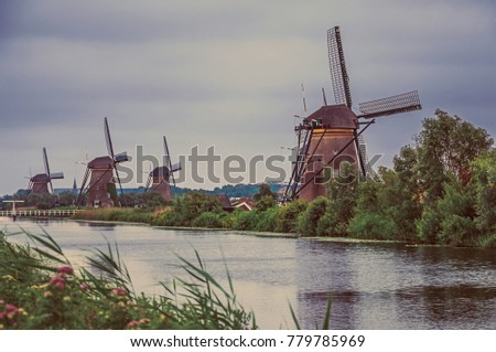 canal with bushes and windmills ...
