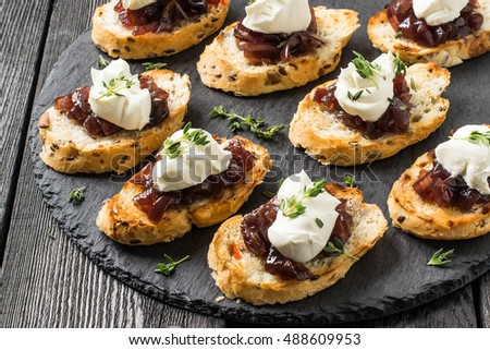 Shutterstock Canape or crostini on slate board. Ideal as an aperitif. Ingredients: toasted baguette with sunflower and flax seeds, onion jam, cream cheese and fresh thyme
