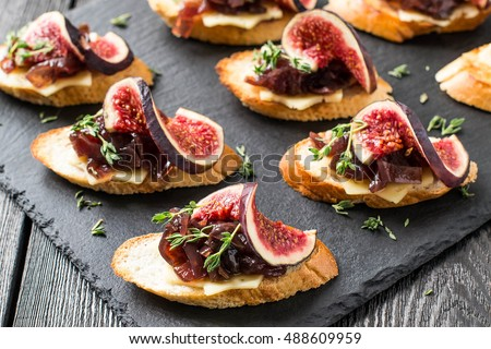 Canape or crostini with toasted baguette, cheese, onion jam, figs and fresh thyme on a slate board. Delicious appetizer, ideal as an aperitif. Selective focus