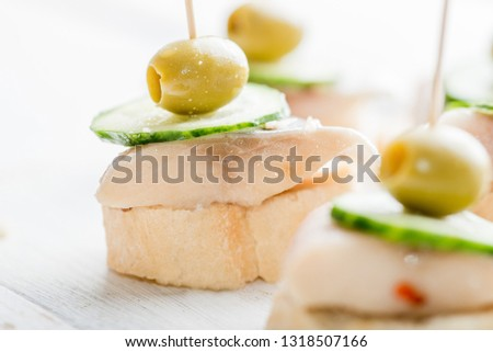canape with a piece of fish and olive on a light background #1318507166