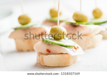 canape with a piece of fish and olive on a light background #1318507169