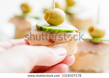 canape with a piece of fish and olive on a light background #1318507178