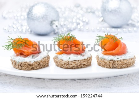 canape with rye bread, cream cheese, salmon and greens for Christmas, close-up