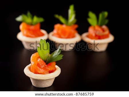 Canape with smoked salmon fish on black background