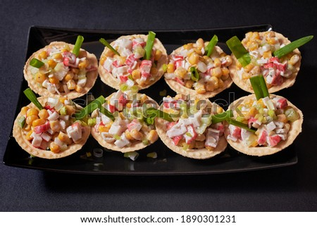 Canapes in tartlets, tasty snack. Tartlets with crab sticks and canned corn salad on a black rectangular plate. Black background.