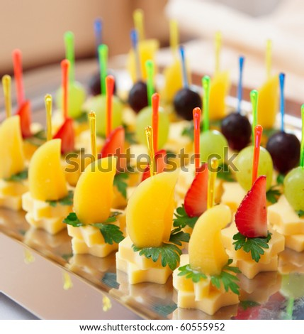 Canapes of cheese with fruits, close-up shot