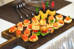 Canapes of different types on the buffet table. Tiny sandwiches set on skewers that can be sent to the mouth as a whole without biting off a piece.