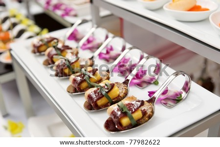 Canapes with cured ham (jamon or prosciutto) on banquet table, selective focus