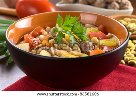 Canary bean soup with meatballs and other vegetables garnished with a parsley leaf (Selective Focus, Focus on the meatball in the front)