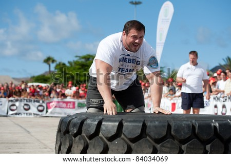 CANARY ISLANDS - SEPTEMBER 03: Jimmy Laureys (l) from Belgium lifting and rolling a wheel (weights 400kg) during Strongman Champions League in Las Palmas September 03, 2011 in Canary Islands, Spain