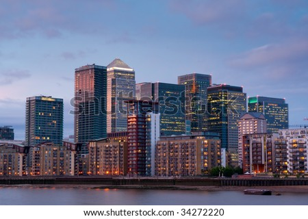 canary wharf, london's new financial district, by thames river at dusk, with scattered residential apartment block